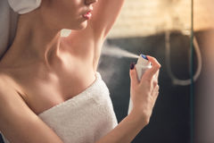 Girl in the bathroom. Beautiful girl in bath towel is applying deodorant while standing in bathroom after having a shower Stock Photos