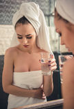 Girl in the bathroom. Beautiful girl in bath towel is feeling pain, holding a glass of water and looking into the mirror in bathroom stock images