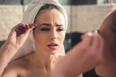 Girl in the bathroom. Beautiful girl in bath towel is plucking eyebrows while looking into the mirror in bathroom royalty free stock images