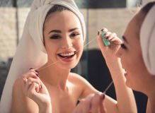 Girl in the bathroom. Beautiful girl in bath towel is using a dental floss and smiling while looking into the mirror in bathroom stock images