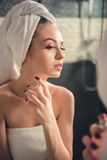 Girl in the bathroom. Beautiful girl in bath towel is using perfume while looking into the mirror in bathroom royalty free stock photo