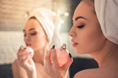Girl in the bathroom. Beautiful girl in bath towel is using perfume while looking into the mirror in bathroom stock photography