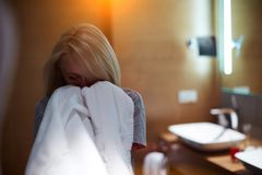 Girl in the bathroom enjoying the smell of fresh white towels stock images