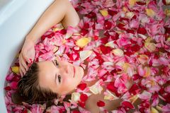 Girl in the bathroom with rose petals, close up portrait. The girl in the bathroom with rose petals, close up portrait royalty free stock photo