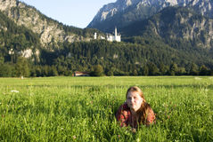 Girl in Bavaria, Germany. Girl sitting in the grass near Neuschwanstein Castle royalty free stock photo