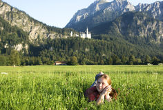 Girl in Bavaria, Germany. Girl sitting in the grass near Neuschwanstein Castle stock photos