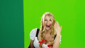 Girl in bavarian costume lures to their hand and showing the thumb. Green screen. Blonde woman in bavarian national costume peeking from behind a board and stock video footage