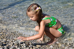 Girl on beach. Plays sea stone Stock Photo