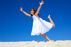 Girl on the beach. A little girl in white dress with her hands spread like wings, playing on a the beach sands Stock Image
