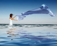 Girl on the beach. Girl in a blue dress with a cloth on the beach Stock Images