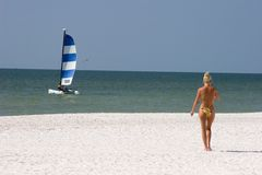 Girl on the Beach. Girl Walking on the Beach with Catamaran in Background Royalty Free Stock Photos