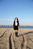 Girl on the beach. A young woman stands in the autumn beach Stock Photo