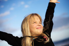 Girl at beach. Girl with happy smile at beach with arms raised Stock Photo