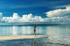 Girl on a beach. Girl on a tropical beach with outstretched arms Stock Images