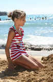 Girl on beach. A smiling young girl on the sand near the sea Royalty Free Stock Images