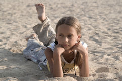 Girl on the beach. Dressed girl lying on a beach in his stomach and looks in front of her Stock Photography