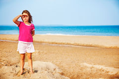Girl at the beach. Little girl salutes standing on smushed sand castle at the beach Stock Images