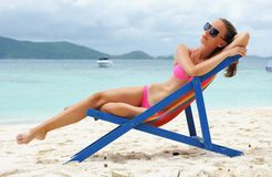 Girl on a beach. Girl on a tropical beach sitting in chaise lounge Royalty Free Stock Images