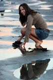 Girl at the Beach. Young teen brunette looking for shells on the beach stock photo