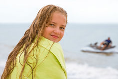 Girl on the beach. Girl with long blond hairs on the beach.  Jet ski in background Royalty Free Stock Image