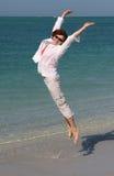 Girl on the Beach. Happy girl on the beach jumping with joy stock photo