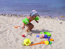 Girl on the beach. Little girl playing with toys on the beach, in Greece Stock Photo