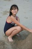 Girl at the beach. Girl smiling and playing sand by the beach Royalty Free Stock Images