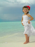 Girl on the beach. Little girl on the beach in white dress with flower Royalty Free Stock Photos