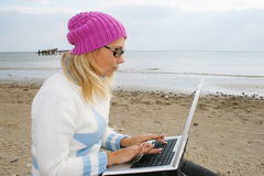 Girl on a beach. With a notebook royalty free stock photography
