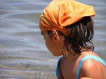 Girl at beach. Little girl with scarf, at the beach Royalty Free Stock Image