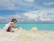 Girl on the beach. Girl plaing with sand on the beach Royalty Free Stock Images
