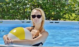 Girl and beach ball. Teen girl holds beach ball with dark sunglasses and long blonde hair in the family pool Stock Photo