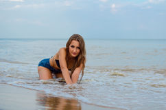 Girl on the beach. Beautiful girl sitting on the beach royalty free stock image