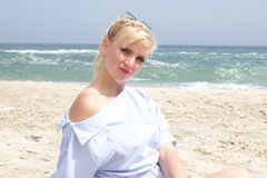 The girl on the beach, the blonde by the sea. Girl in blue dress royalty free stock images