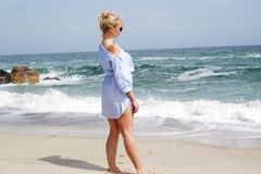 The girl on the beach, the blonde by the sea. Girl in blue dress royalty free stock photo