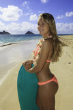 Girl on the beach with boogie board. Beautiful girl on the beach in bikini with boogie board Royalty Free Stock Photo