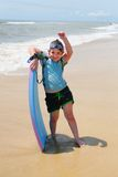 Girl on the Beach Boogie Boarding. Young girl playing on the beach with a boogie board royalty free stock photography