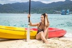 Girl on the beach with a canoe. A girl in a swimsuit is sitting on the beach with a canoe royalty free stock photography