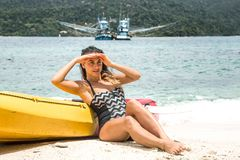 Girl on the beach with a canoe. A girl in a swimsuit is sitting on the beach with a canoe stock photography