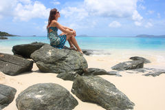 Girl on a beach in the caribbean. Young woman sitting on a tropical beach relaxing Royalty Free Stock Images