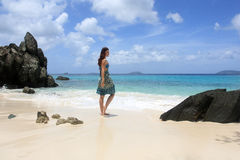 Girl on a beach in the caribbean. Young woman on a tropical beach relaxing Stock Image