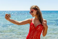 Girl on the beach with a cell phone making selfie on sunny day stock photos