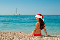 Girl on the beach in a Christmas hat. New Year's meditation on the beach. Girl on the beach in a Christmas hat Stock Photography