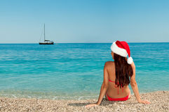 Girl on the beach in a Christmas hat. New Year's meditation on the beach. Girl on the beach in a Christmas hat Royalty Free Stock Photo