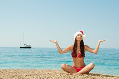 Girl on the beach in a Christmas hat. Stock Image