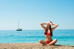 Girl on the beach in a Christmas hat. New Year's meditation on the beach. Girl on the beach in a Christmas hat Stock Images