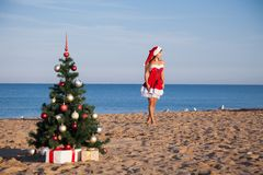 Girl on the beach on Christmas and new year at the resort. Girl in costume on the karnovalnom resort on Christmas new year Stock Photo