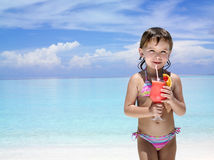 Girl on the beach with cocktail. Little girl on the beach drinking exotic cocktail Stock Photography