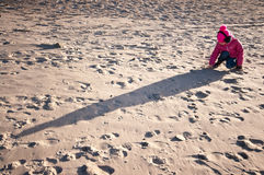Girl on beach in cold. Girl dressed in coat and ear muffs playing on sandy beach with long shadows royalty free stock photo