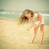Girl on the beach collecting shells Stock Images
